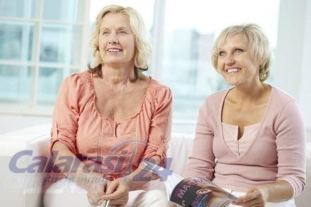 Portrait of two senior women sitting on sofa